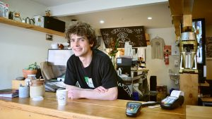 young man working at coffee counter