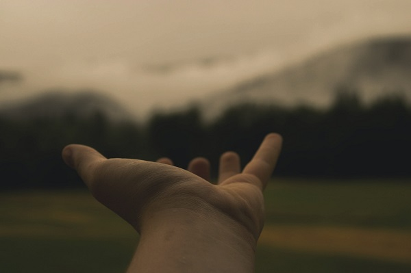 Outstretched hand with mountains in background