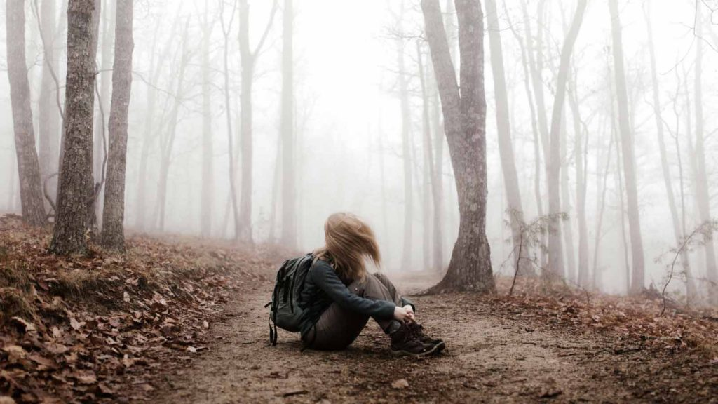 girl wearing backpack sits on a forest path