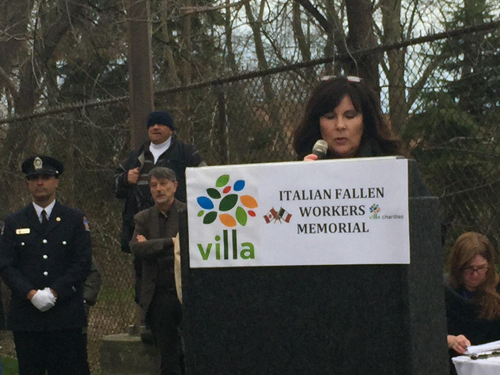 Erin Pitruzella speaks at podium for Italian Fallen Workers Memorial