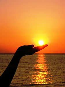 silhouette of hand under the sun