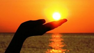 Silhouette of hand cupping under the setting sun over a body of water