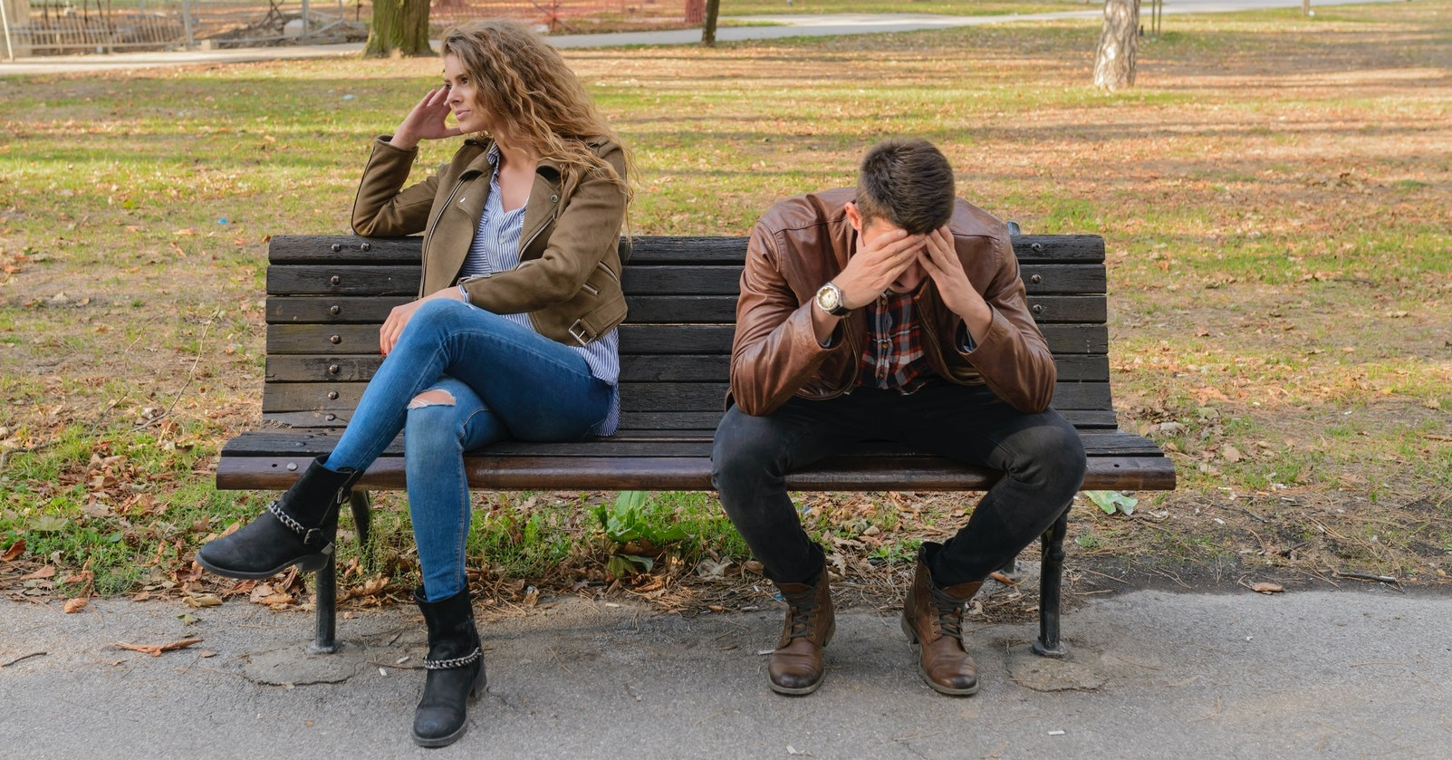 Two people sitting on park bench not talking
