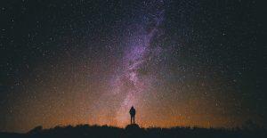 Woman staring up at night sky
