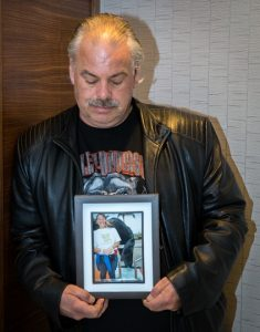 Man holding framed photo of woman
