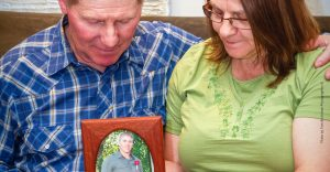 Mom and Dad hold framed photo of son