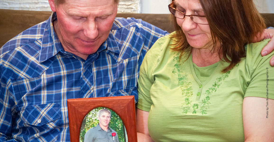 Dad and mom holding framed photo of son
