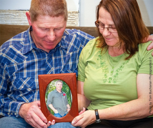 Dad and Mom hold framed photo of son
