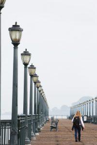 Woman walking down a boardwalk