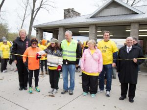 A group of people wearing jackets and yellow T-shirts gather for a ceremonial ribbon cutting