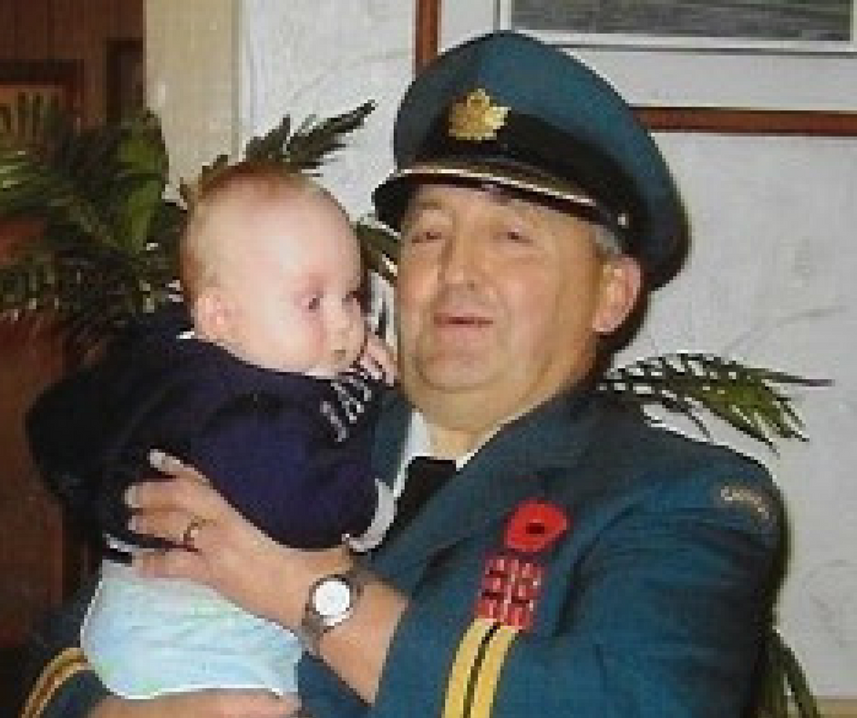 Older man in uniform holding baby