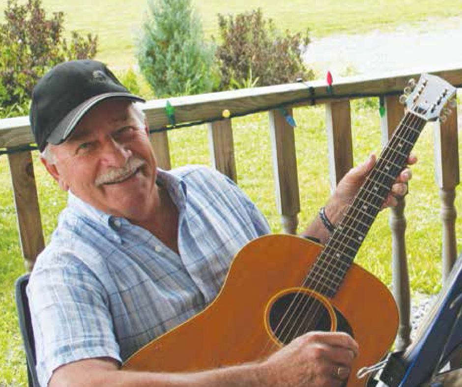 Man holding guitar while sitting on porch