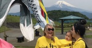 Two women, one holding a toddler, stand with Mount Fuji in the background.