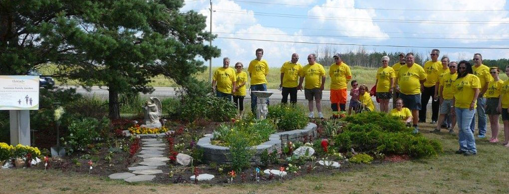 group of people wearing yellow t-shirts stand at an outdoor garden