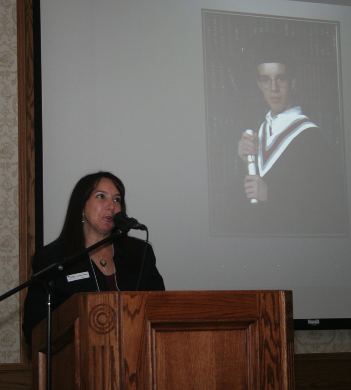 woman speaking into microphone at podium with young man's graduation photo projected behind her