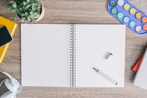 A notebook lies open on a table with a pen and other writing tools handy.