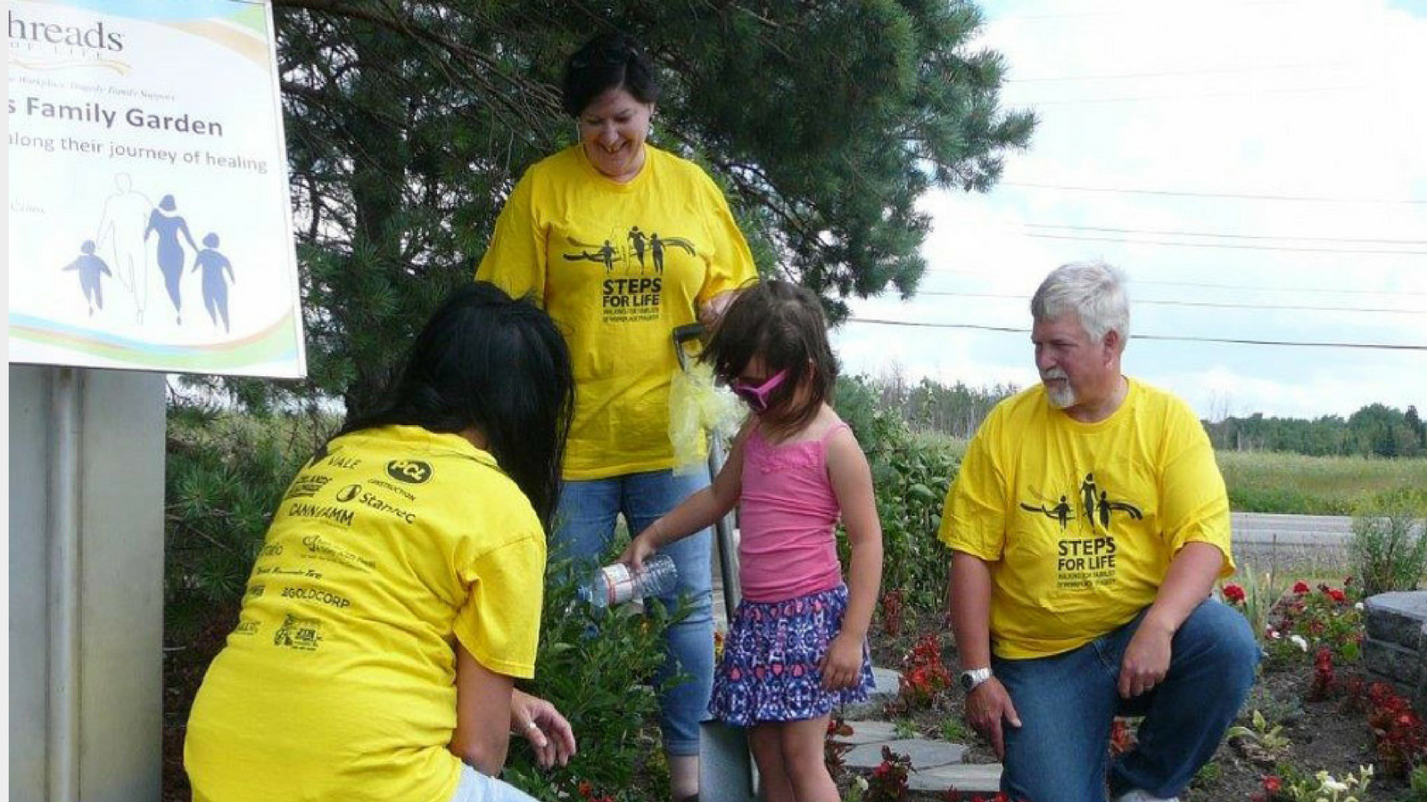a young girl waters flowers while three adults in yellow t-shirts watch on
