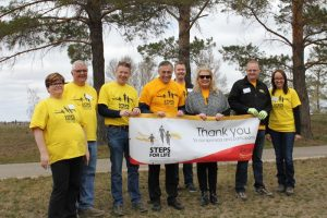 People in yellow T-shirts hold a sign thanking sponsors and participants