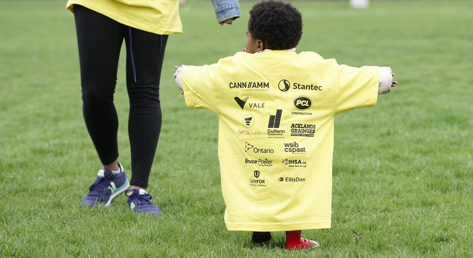 Young boy shows off the back of his oversized t-shirt with names of event sponsors