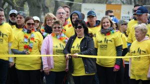 Group of people cutting the ribbon to start fundraising walk.