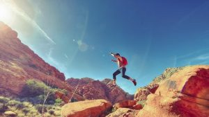 Man jumping through the air with desert landscape in the background