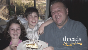 Man holds Happy Birthday cake with young girl and boy