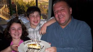 young girl, young boy, man, hold plate with cheesecake and syrup that reads happy birthday