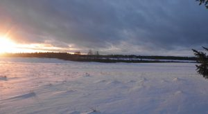 Sun rising over a snow-covered field
