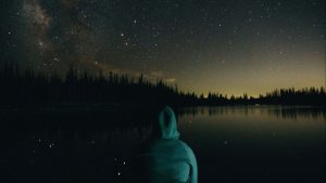 Person wearing hoodie sweatshirt looking out over a lake under starlight