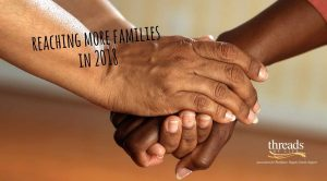 """two hands clasped with text reading """"reaching more families in 2018"""""""
