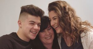 smiling woman hugging young man and woman