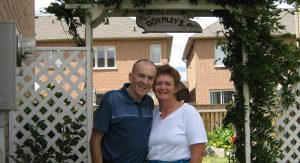 Couple smiling together under an arbour.