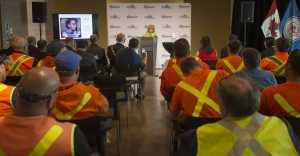 Audience of workers in high-visibility clothing, listens to a woman speaking at a podium
