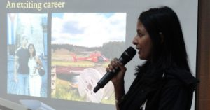 """Woman holding microphone speaks in front of projected photos with title """"An Exciting Career"""""""