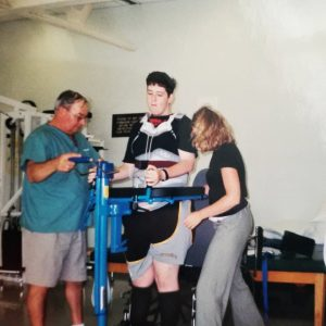 Young man is assisted to walk by physiotherapists