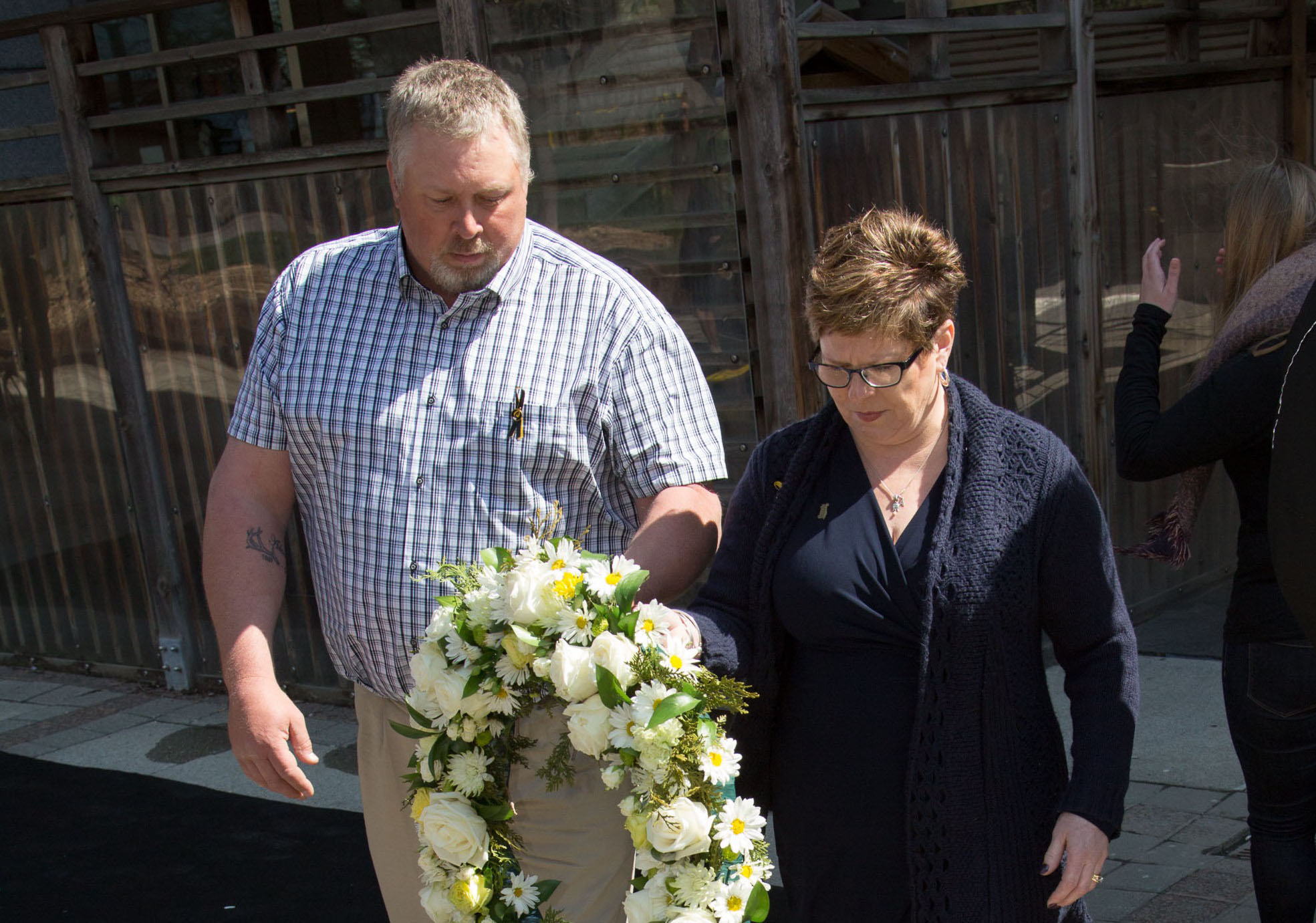 Man and woman carry yellow and white wreath