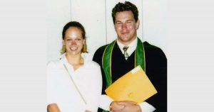 Young woman and man in graduation clothing smile for camera