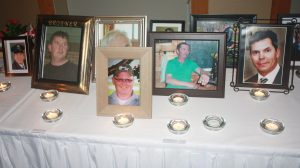 Framed photographs and lit candles are arranged on a table