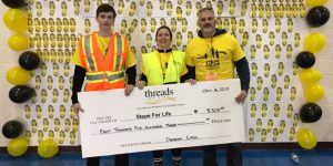 A woman standing with her son and husband, holding a big cheque