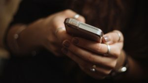 woman holding cell phone in hands