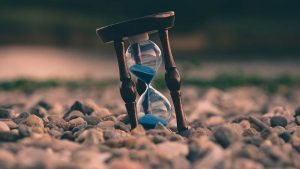 timer with blue sand rests in gravel