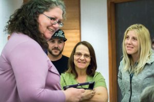Smiling woman with curly grey hair holds tablet as two women and a man watch