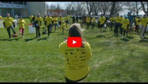Video still of people in yellow t-shirts warming up before the walk
