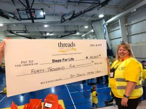Smiling woman stands in front of presentation cheque made out to Steps for Life for $40,005.53