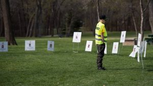 Young man in yellow volunteer vest reads signs in the grass