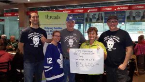 """Three men and two women stand holding a sign that reads """"2018 EllisDon Hockey Tournament to Threads of Life $5,600"""""""