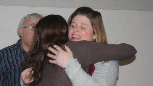 two women hug with man looking on