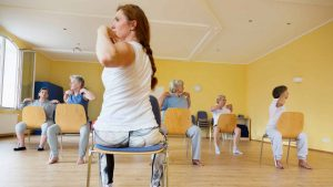 Instructor leads group of senior women in chair yoga class