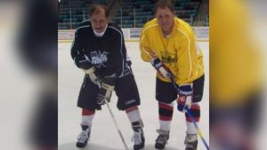 Two older men in hockey gear stand with sticks on the ice