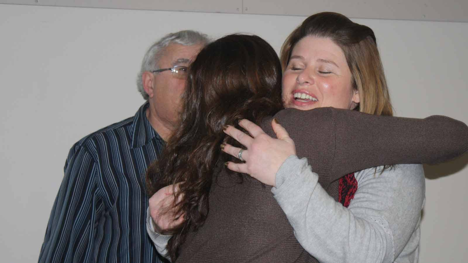 Woman with blonde hair hugs person with long brown hair as an older man looks on